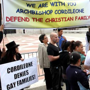 Melanie Nathan, protesting under the anti-gay sign by supporters of Cordileone. Screenshot from Photo by Kristina Lapinski