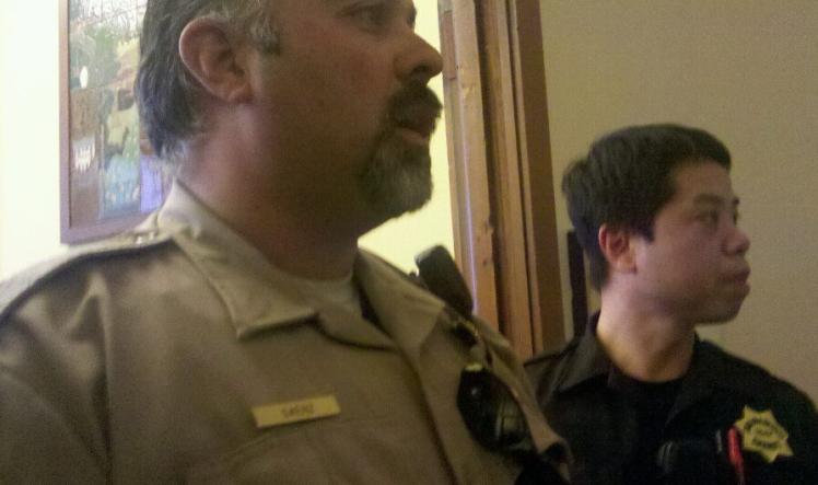 Officer Saenz blocks door to press