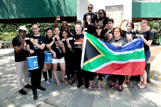 Alan Demby gifting Mandela Day Studentmvolunteers in NYC with Mandela Tokens and SA Flag JPG