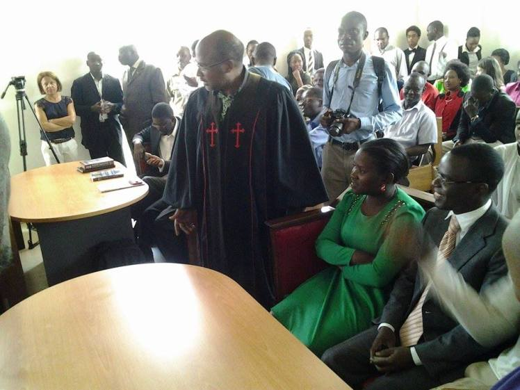 Plaintiff Frank Mugisha can be seen smiling after ruling announced, while Anti-Gay Martin Ssempa in robe looking on in dismay.