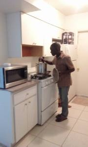 Andrew Standing in his new kitchen, shared with 3 other refugees from African countries.