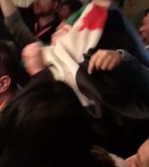 A protester smothers a Jewish man wearing a yamulkah, with a Palestinian flag, attacking him from behind.