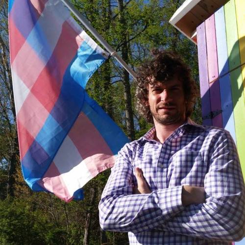 Neal Gottlieb outsise the rainbow OUTHOUSE with Trans Flag attached